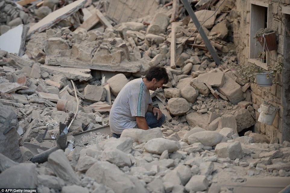 Grief: Uma soluços italiana nos escombros fora de sua casa danificada como as pessoas diziam vilas e cidades foram destruídas pelo terremoto de magnitude 6,2