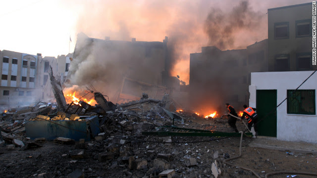 Palestinians extinguish a fire after Israeli airstrikes targeted the Interior Ministry building in Gaza City Friday.