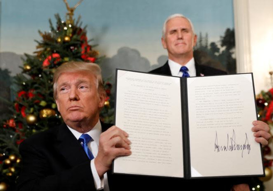U.S. Vice President Mike Pence stands behind as U.S. President Donald Trump holds up the proclamatio
