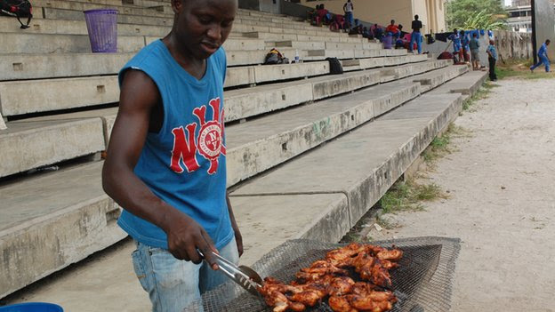 A man barbequing meat a cricket venue in Lagos, Nigeria