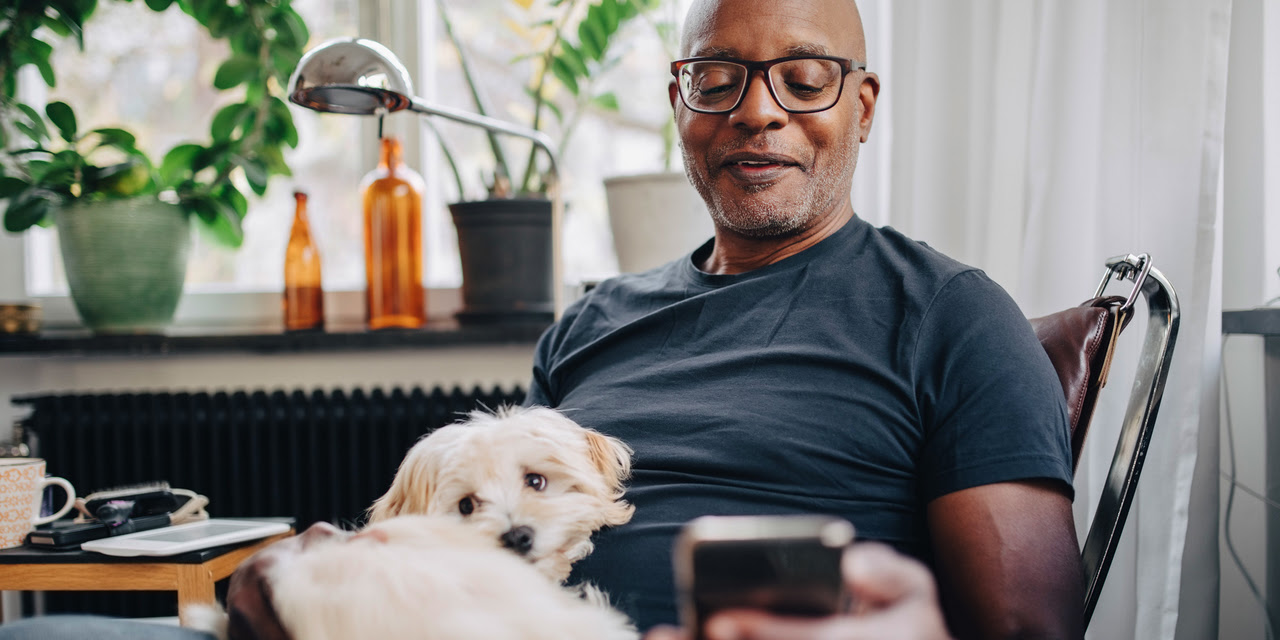 Senior man with dog on lap looking at cell phone