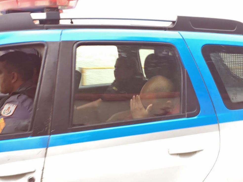 PM preso na megaoperação esconde o rosto ao ser levado por outros policiais (Foto: Fernanda Rouvenat/G1)