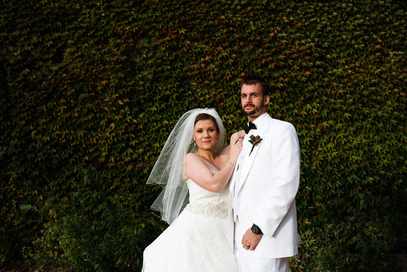 The Bride and Groom get photos taken around in downtown Rockford Illinois in front of a vine covered wall following their wedding at Court Street United Methodist Church for an Autumn wedding before heading to their Reception at Rockford Women's club.