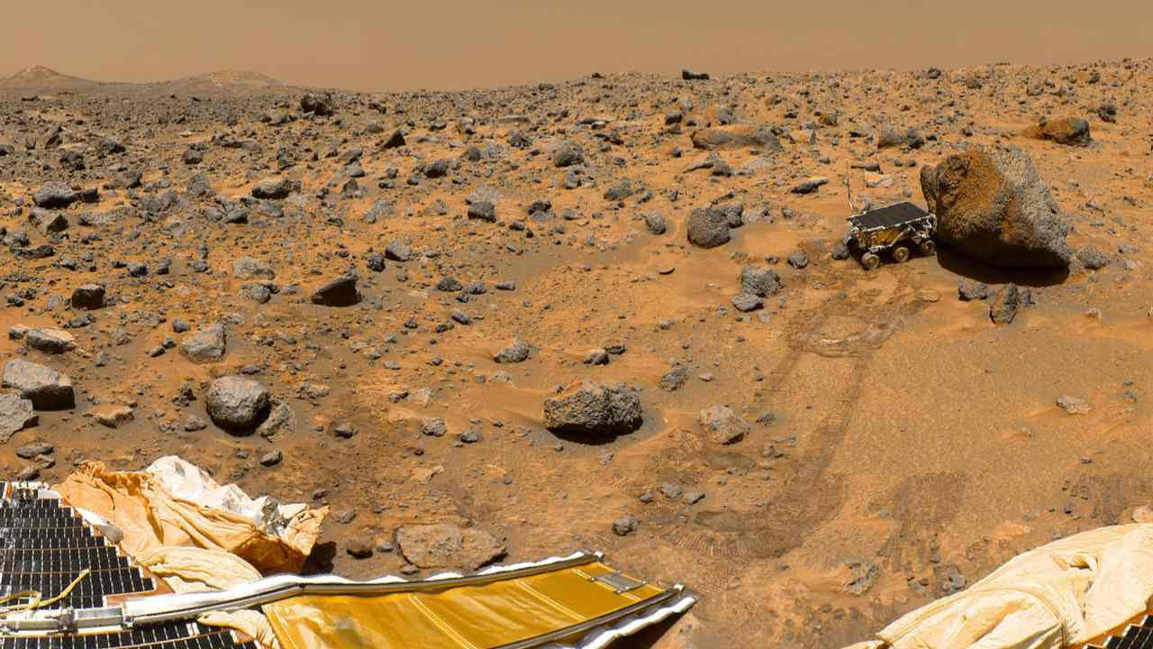 """This portion of a classic 1997 panorama from the IMP camera on the mast of NASA's Mars Pathfinder lander includes """"Twin Peaks"""" on the horizon, and the Sojourner rover next to a rock called """"Yogi."""" Image credit: NASA/JPL"""