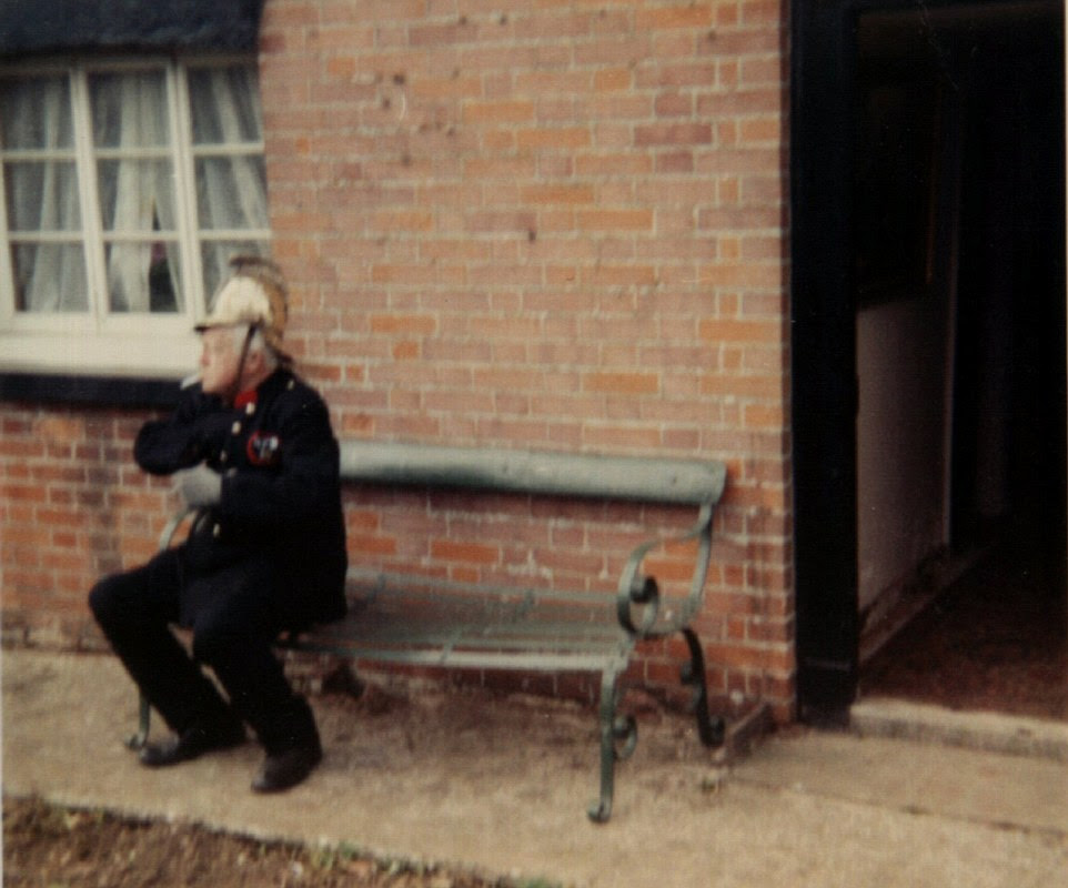 Arnold Ridley, wearing what appears to be a fireman's uniform, sits on a bench in Thetford. These images are all that survives to document the Thetford filming, as the BBC either ditched or lost the other records