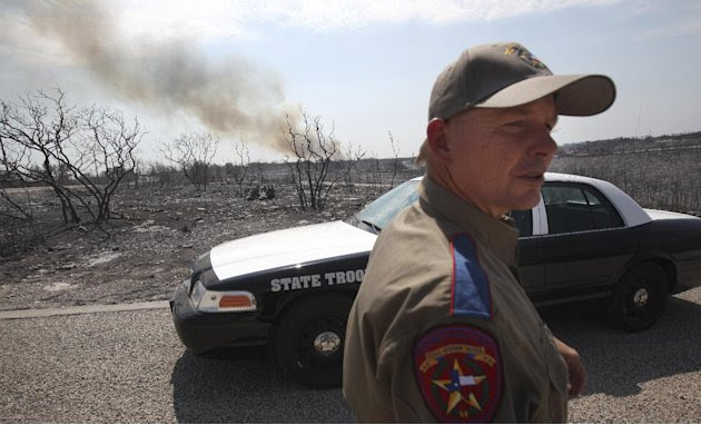Texas State Trooper Garry Allen stands guard in an area destroyed by a wildfire at Possum Kingdom Lake, Texas, Wednesday, Aug. 31, 2011. (AP Photo/LM Otero)