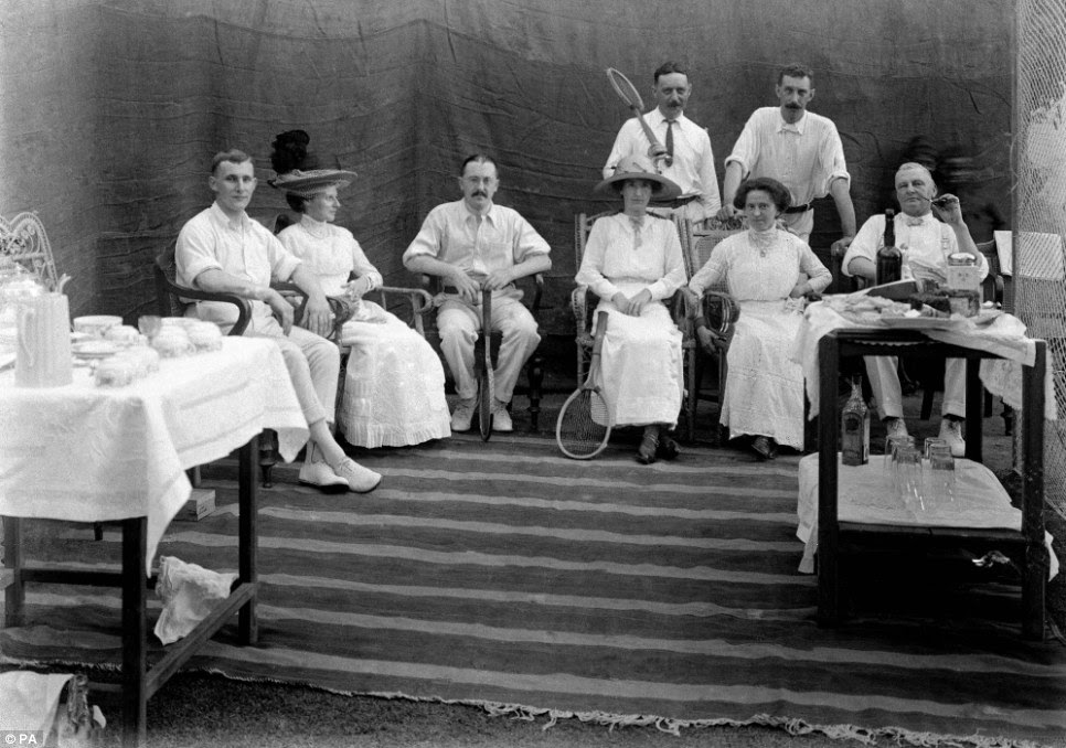 A tennis party (one, far right, with a pipe) poses among tea trolleys in this photo taken in India around a century ago