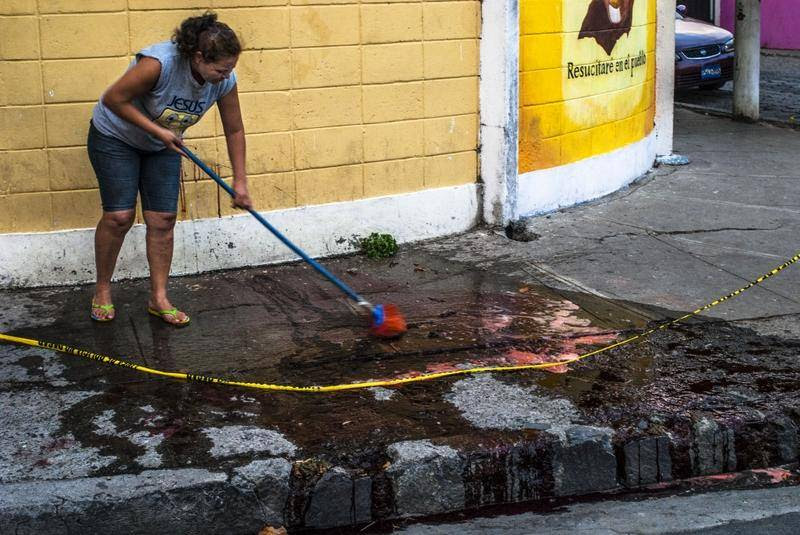 Et familiemedlem vasker blodet væk fra gaden, hvor den 33-årige Edgar Giovanni Morales blev skudt i 2013. Morales var tidligere medlem af Mara Salvatrucha, men arbejdede nu sammen med præsten Antonio Rodriguez om at hjælpe bandemedlemmer med at forlade gangster-tilværelsen. Morales blev mejet ned uden for Rodiguez' kirke i Mejicanos i El Salvador. (Foto: All Over Press)