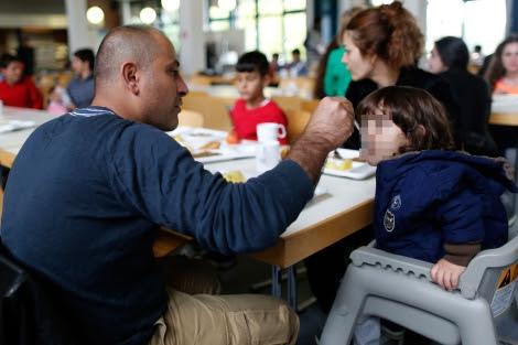 Un padre dando de comer a su hija.| Ina Fassbender | Reuters