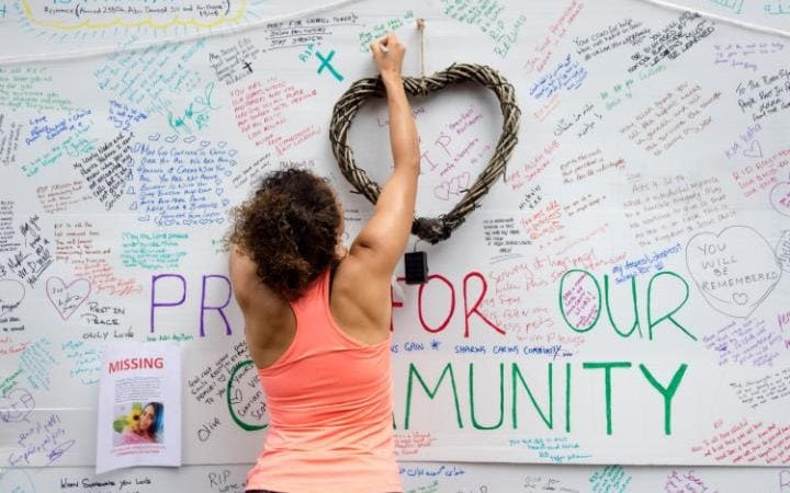 People writing messages of condolence on the wall of the Latymer Church after the fire in Grenfell Tower in London, UK.