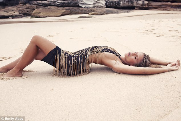 Provocative: In one sultry snap Natasha arched her back as she lay on the sand at Sydney's Tamarama Beach