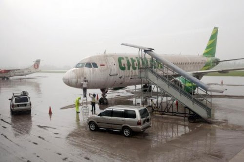 Workers stand near a Citilink airplane covered with ash from Mount Kelud at Adi Sucipto airport in Yogyakarta