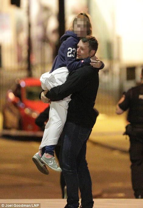 Um pai leva sua filha embora depois do ataque terrorista no concerto de Ariana Grande