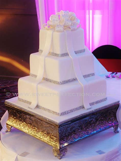 Three tiered ivory square wedding cake, with diamante trim