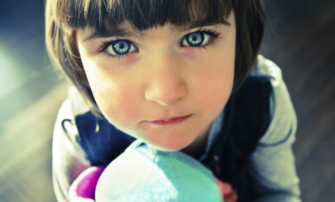 FOTO: Uma menina, de olhos azuis, segurando um bichinho de pelúcia