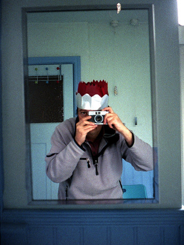 reflected self-portrait with Yashica Mimy camera and xmas hats on 12th night by pho-Tony