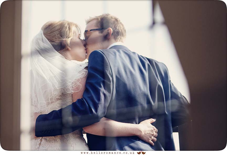 Bride and Groom kissing on Balcony at Woodhall Manor, shot from inside - www.helloromance.co.uk
