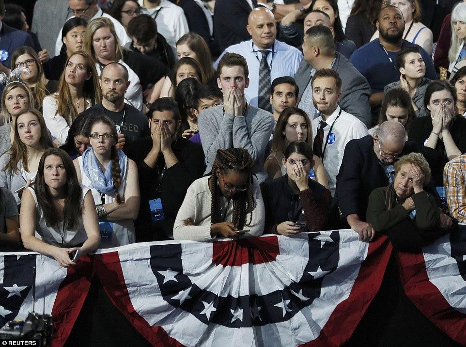 apoiantes de Hillary Clinton segurar suas mãos à boca como eles reagem a resultados eleitorais durante a noite comício eleitoral do candidato democrata