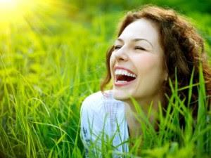 femme qui sourit dans un champ, attirer le bonheur