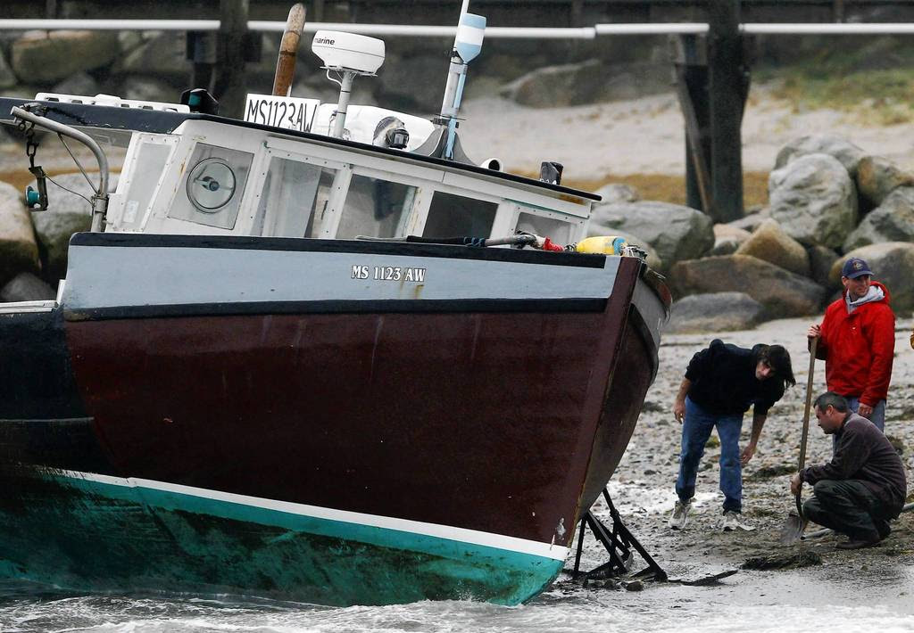 Men try to save a boat which became unmoored and washed up on shore due to high winds from Hurricane Sandy in Scituate, Massachusetts.