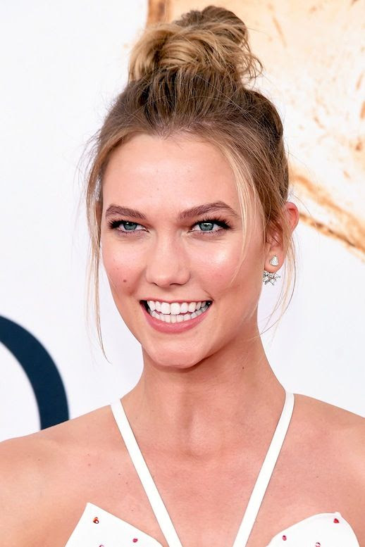 Le Fashion Blog Model Style Karlie Kloss Easy Top Knot Hairstyle White Top Via Harpers Bazaar