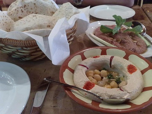 Counterclockwise from bottom right: hommos, kebbeh nayeh, and pita bread