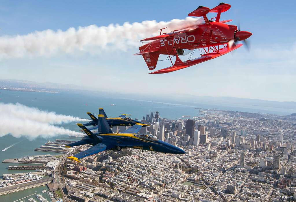 The US Navy Blue Angels numbers 5 and 6 fly below Sean Tucker (above) as he pilots the Oracle Challenger III over San Francisco, California as part of a practice run for Fleet Week on October 6, 2016.  Photo: JOSH EDELSON, AFP/Getty Images