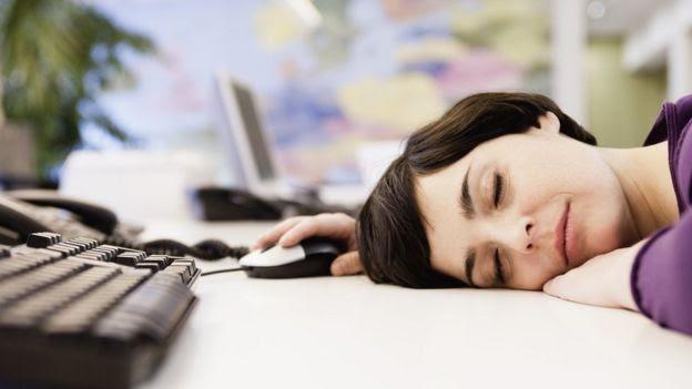 Mulher adormece sobre teclado do computador