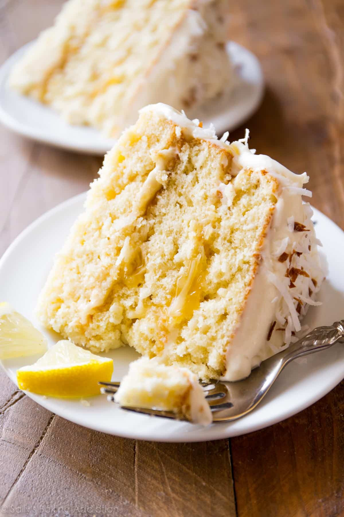 Lemon coconut cake, with deliciously moist coconut cake layers, homemade lemon curd, toasted coconut and cream cheese frosting, is a family favorite! sallysbakingaddiction.com