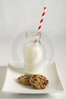 Milk and cookies white background with red striped straw