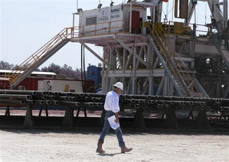 A Chesapeake Energy Corp. worker walks past stacks of drill pipe needed to tap oil and gas trapped deeply in rock like shale at a Chesapeake oil drilling site on the Eagle Ford shale near Crystal City, Texas, June 6, 2011. REUTERS/Anna Driver