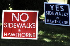 Signs for and against new sidewalks line the streets.