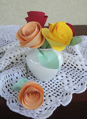Vasos para enfeitar a mesa com rosas de papel coloridas