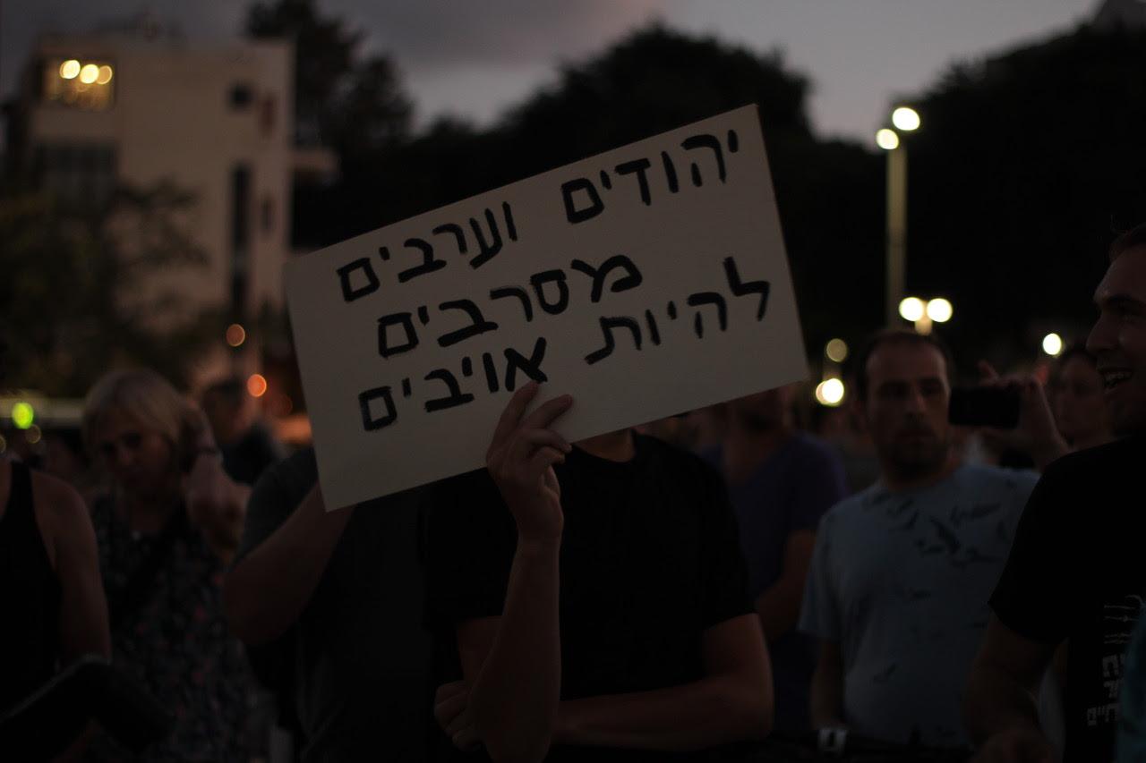 """Un manifestant pro-palestinien, lors du rassemblement du 17 juillet 2014 au soir. Sur la pancarte on peut lire: """"Israéliens et Arabes refusons d'être ennemis"""""""