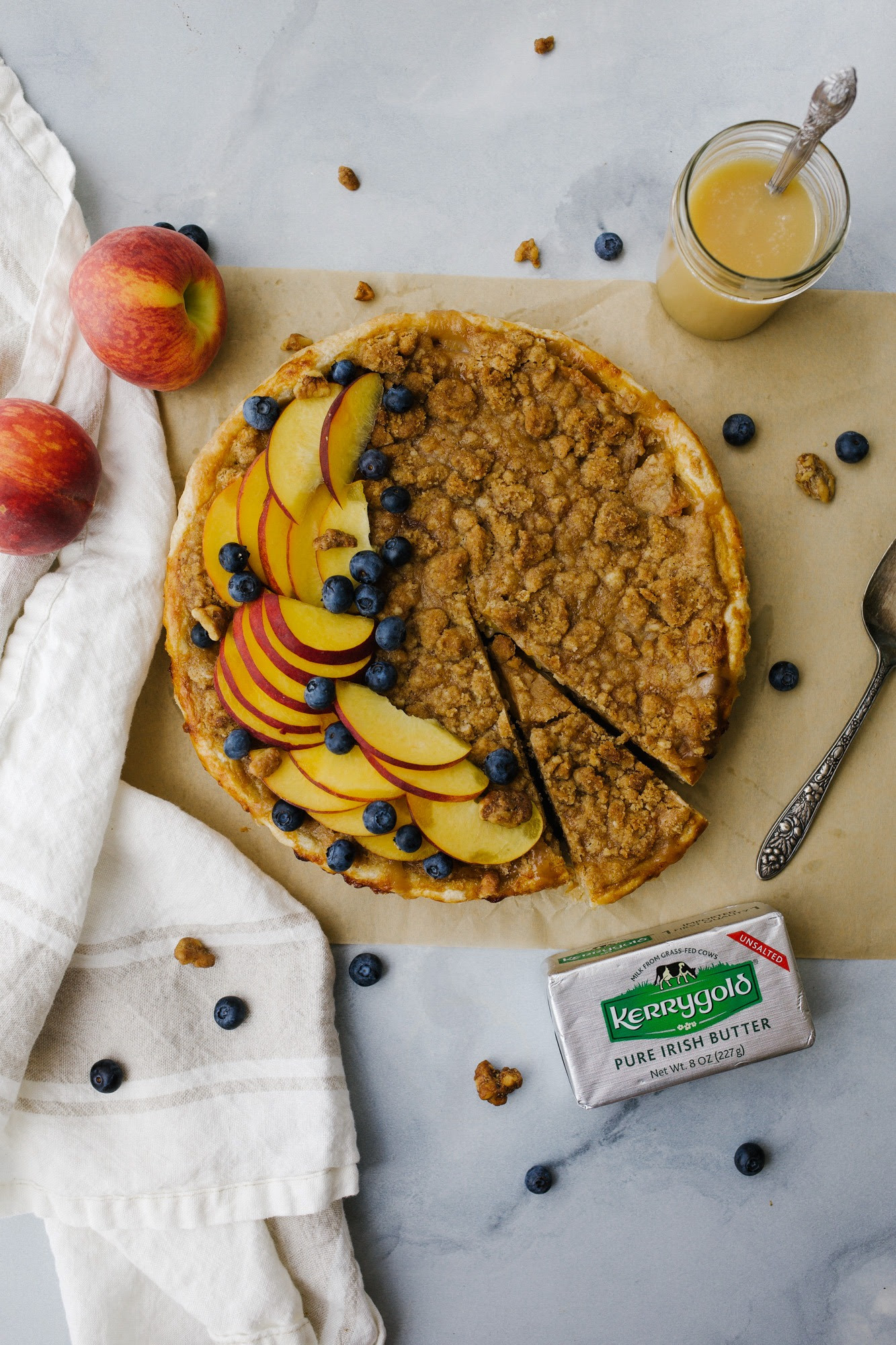 Honey Peach Pie by Wood and Spoon. This is an all butter pie crust filled with a honey caramel and fresh peaches and topped with a brown butter crumble. This pie bakes up scented with honey and juicy peaches and the crust and crumble add a bit of salt to offset the sweet. This is a great summer recipe to use fresh produce and make homemade pie tarts. Learn more about this dessert for a crowd at thewoodandspoon.com