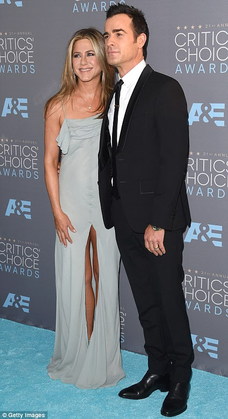 Feeling daring: Jennifer Aniston wore a floaty Saint Laurent by Hedi Slimane gown with a VERY high split as she arrived with husband Justin Theroux (sporting a Givenchy suit)