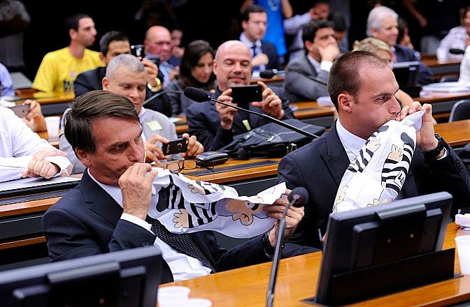 (Bolsonaro pai e Bolsonaro filho com a boca no pixuleco)
