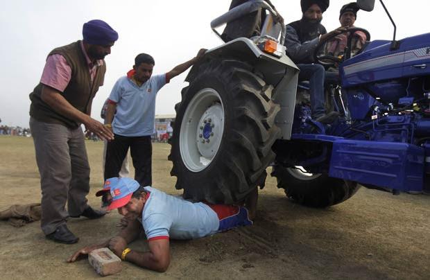 Homem se deixa atropelar por trator com três pessoas durante festival rural em Kila Raipur, próximo à cidade indiana de Ludhiana. A demonstração de força é parte do festival esportivo conhecido como 'Olimpíadas Rurais da Índia' (Foto: Altaf Qadri/AP)