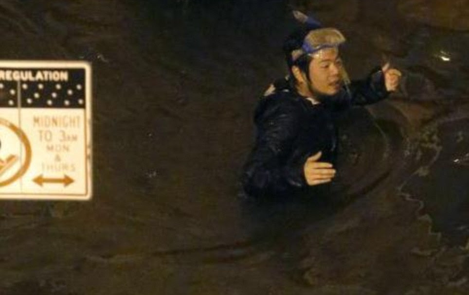 Above waist high: A man wearing a snorkel is seen wading through the water in New York City on Monday night