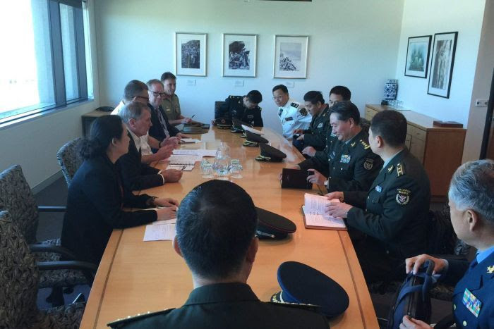 Men and women in uniform meet around a table