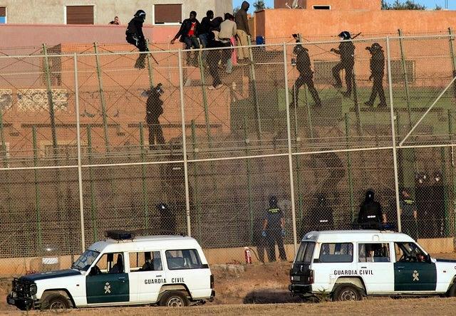 <p>Migrantes africanos sobre la valla fronteriza, mientras agentes de la Guardia Civil española tratan de alcanzarlos, durante su intento de cruzar la frontera a territorio español, desde Marruecos al enclave norteafricano español de Melilla, el 14 de agosto de 2014.</p>