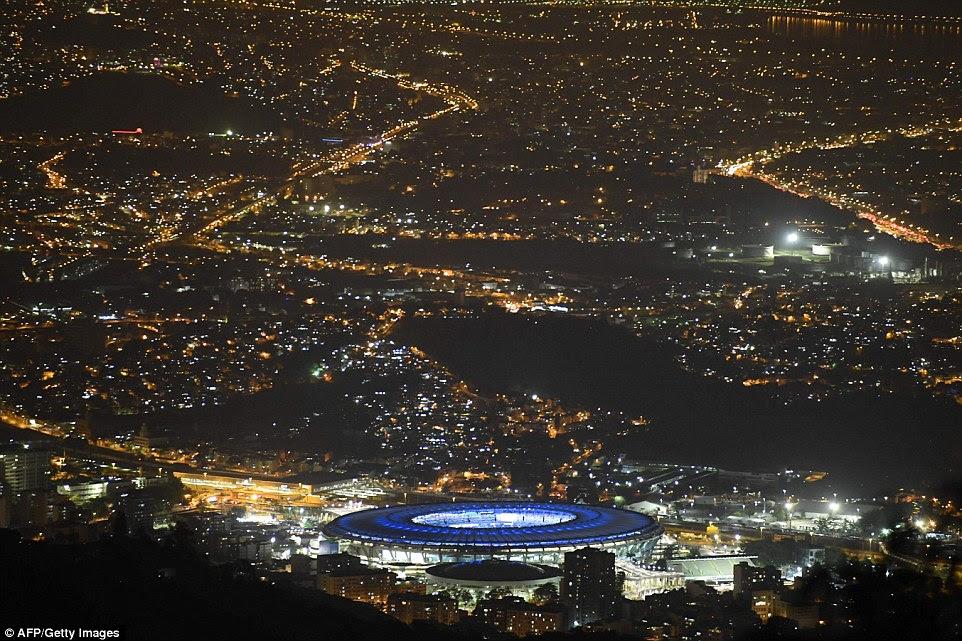 Dezenas de milhares de fãs de streaming para o Estádio do Maracanã para a cerimônia eram guardados por quase tantos policiais e soldados fortemente armados (foto é o estádio visto iluminada à noite para a cerimônia)