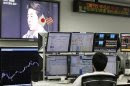 An employee of a foreign exchange trading company looks at monitors as a television set shows Japan's incoming Prime Minister and the leader of Liberal Democratic Party (LDP) Shinzo Abe speaking in Tokyo