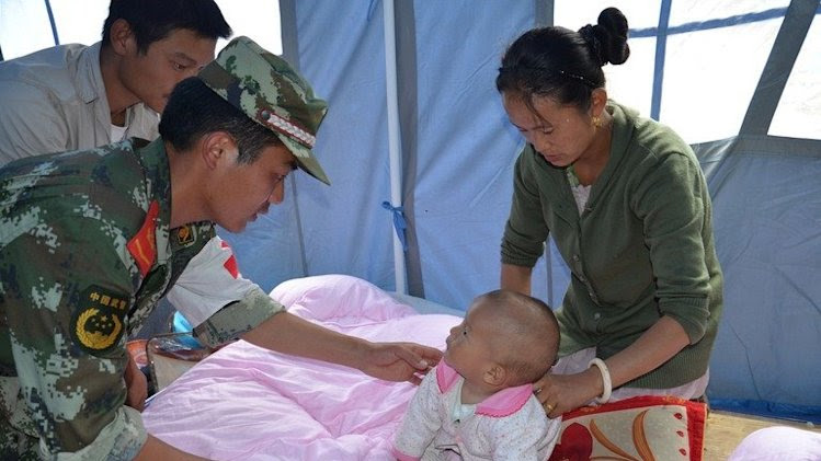 Rescuers take care of a baby following an earthquake in Deqin, southwest China's Yunnan province on August 31, 2013
