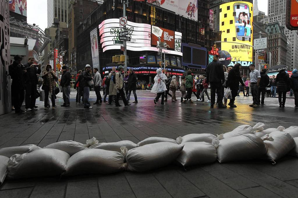 People walk by sand bags in front of a building in Times Square as Hurricane Sandy begins to affect New York City. The storm, which threatens 50 million people in the eastern third of the U.S., is expected to bring days of rain, high winds and possibly heavy snow. New York Governor Andrew Cuomo announced the closure of all New York City will bus, subway and commuter rail service as of Sunday evening.