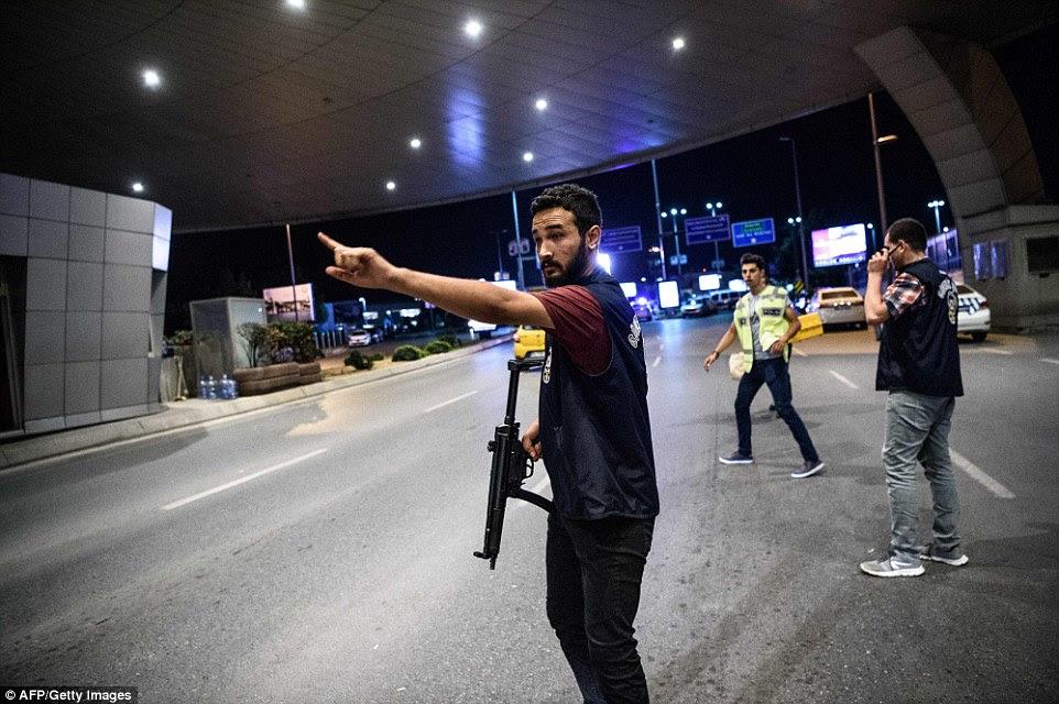 Um oficial da polícia armada turco ajuda a controlar o tráfego no portão principal do aeroporto de Ataturk após explosões e tiros irromperam no terminal