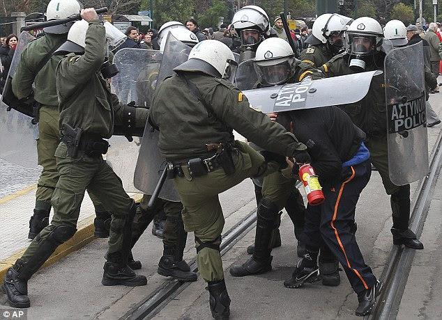 Περιτριγυρισμένο: Ένας διαδηλωτής έχει κλώτσησε και χτύπησε με κλομπ ως αξιωματικοί κίνηση για να τους κρατούν