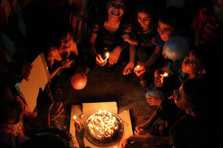 Un grupo de niños de Gaza celebra un cumpleaños alumbrados con velas