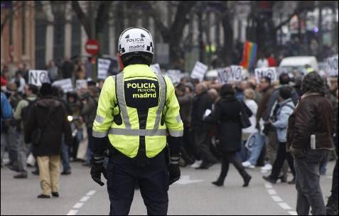 Un agente de movilidad observa cómo los manifestantes cortan el segundo carril de la calle Alcalá durante la 'marea blanca'.