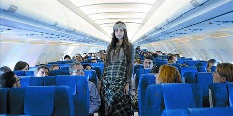 Una modelo vestida de Ian Mosh, ayer, en el pasillo del avión con destino a Barcelona del vuelo JK-426 de Spanair.